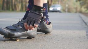 La muchacha de Triathlete aprieta los zapatos del camino ante raza Concepto del Triathlon C?mara lenta metrajes