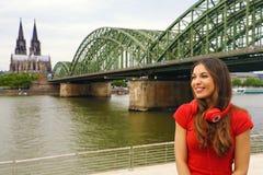 La muchacha de la vida de ciudad con el auricular y la camiseta roja disfrutan de su tiempo libre en Colonia, Alemania imagen de archivo libre de regalías
