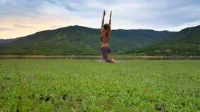 La muchacha de la vista lateral aumenta las manos en actitud de la yoga en el banco del lago