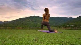 La muchacha de la vista lateral del abejón celebra actitud de la yoga en rodilla en el prado del lago