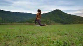 La muchacha de la vista lateral de Flycam lleva a cabo actitud de la yoga contra las colinas del lago