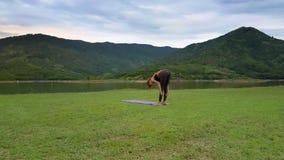 La muchacha de la vista lateral de Flycam lleva a cabo actitud de la yoga en el banco del lago al lado de la colina almacen de metraje de vídeo
