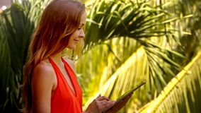La muchacha de la vista lateral practica surf Internet con la tableta por las palmas