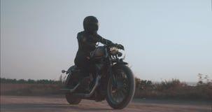 La muchacha de la vista lateral que monta una motocicleta tira encima al lado del camino almacen de video