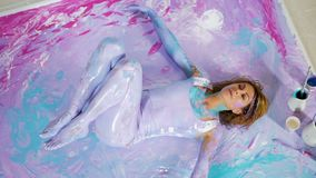 La muchacha de la yoga miente en ella detrás en la pintura en la imagen almacen de metraje de vídeo