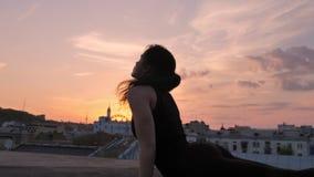 La muchacha de la yogui se está colocando en actitud de la cobra en tejado en verano en la puesta del sol, forma de vida sana, re almacen de metraje de vídeo