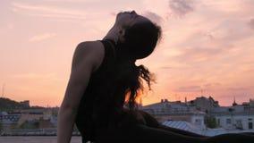 La muchacha de la yogui se está colocando en actitud de la cobra y yendo al tablón en tejado en verano en puesta del sol, la form almacen de metraje de vídeo
