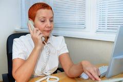 La muchacha del administrador de oficinas marca el número de teléfono Expresión pensativa fotos de archivo