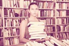 La muchacha del adolescente busca el libro derecho en biblioteca Fotografía de archivo libre de regalías