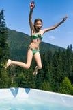 La muchacha del adolescente cae en la piscina al aire libre y grita Foto de archivo libre de regalías