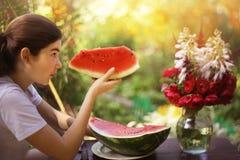 La muchacha del adolescente come la sandía en jardín del verano Fotografía de archivo libre de regalías