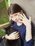 La muchacha del adolescente con dos trenzas muestra la manicura negra con el gato negro Fotos de archivo