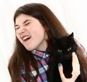 La muchacha del adolescente con el gato negro tiene alergia Foto de archivo