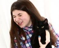 La muchacha del adolescente con el gato negro tiene alergia Imagen de archivo
