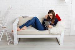 La muchacha del adolescente con PC de la tableta se relaja en casa Imagen de archivo libre de regalías