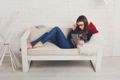 La muchacha del adolescente con PC de la tableta se relaja en casa Fotos de archivo