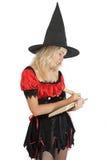 La muchacha del adolescente en la bruja de Víspera de Todos los Santos lee el libro mágico Fotografía de archivo