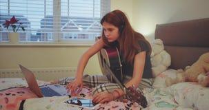 La muchacha del adolescente en su dormitorio que mecanografiaba algo en su cuaderno muy concentró entonces da vuelta en su tablet metrajes