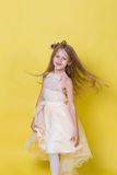 La muchacha del adolescente en un vestido en un fondo amarillo presenta para la cámara Imagenes de archivo