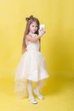 La muchacha del adolescente en un vestido en un fondo amarillo se fotografió en el teléfono Fotografía de archivo