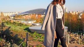 La muchacha del adolescente en una capa gris camina a través del parque Zaryadye en el fondo de un edificio alto en Moscú en a metrajes
