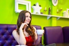 La muchacha del adolescente está bebiendo el café en un café Foto de archivo