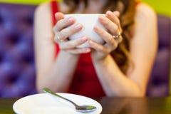 La muchacha del adolescente está bebiendo el café en un café Foto de archivo libre de regalías