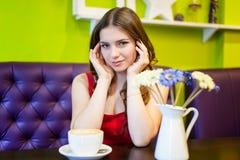 La muchacha del adolescente está bebiendo el café en un café Fotos de archivo libres de regalías