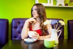 La muchacha del adolescente está bebiendo el café en un café Imagen de archivo libre de regalías