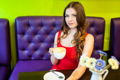 La muchacha del adolescente está bebiendo el café en un café Imagen de archivo