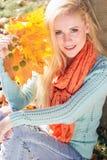 La muchacha del adolescente está sosteniendo las hojas de arce amarillas Imagenes de archivo