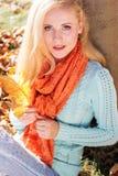 La muchacha del adolescente está sosteniendo las hojas de arce amarillas Imagen de archivo libre de regalías