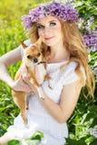 La muchacha del adolescente está sosteniendo su pequeño perro Imagenes de archivo