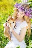 La muchacha del adolescente está sosteniendo su perro Imagen de archivo