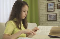 La muchacha del adolescente hace la preparación en la tabla Fotos de archivo libres de regalías