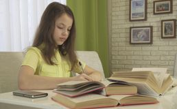 La muchacha del adolescente hace la preparación en la tabla Imagen de archivo