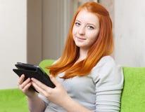 La muchacha del adolescente lee el e-lector o la tableta fotografía de archivo