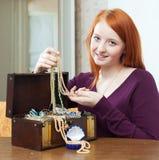 La muchacha del adolescente mira la joyería en cofre del tesoro en casa Fotografía de archivo