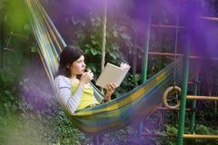 La muchacha del adolescente pone en hamaca con el libro y el gatito Fotografía de archivo libre de regalías