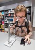 La muchacha del adolescente prueba los auriculares en tienda Imagenes de archivo