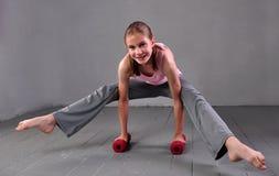 La muchacha del adolescente que hace ejercicios con pesas de gimnasia para convertirse con pesas de gimnasia muscles en fondo gri Imagen de archivo