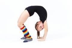 La muchacha del adolescente que hace la gimnasia ejercita en un fondo blanco Fotos de archivo libres de regalías