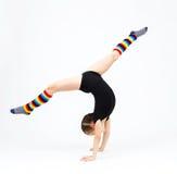La muchacha del adolescente que hace la gimnasia ejercita en un fondo blanco Imagen de archivo libre de regalías
