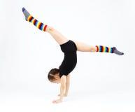 La muchacha del adolescente que hace la gimnasia ejercita en un fondo blanco Imágenes de archivo libres de regalías
