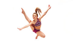 La muchacha del adolescente que hace los ejercicios de la gimnasia aislados en el fondo blanco Imagen de archivo