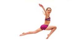 La muchacha del adolescente que hace los ejercicios de la gimnasia aislados en el fondo blanco Foto de archivo