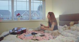 La muchacha del adolescente que juega en Playstation en casa en su dormitorio, tiene un buen rato después de un día escolar duro, almacen de metraje de vídeo