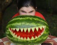 La muchacha del adolescente realiza el moster con la boca cortada sandía de los dientes agudos Foto de archivo libre de regalías
