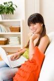 La muchacha del adolescente relaja a casa - feliz con la computadora portátil Imágenes de archivo libres de regalías
