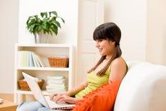 La muchacha del adolescente relaja a casa - feliz con la computadora portátil Imagenes de archivo